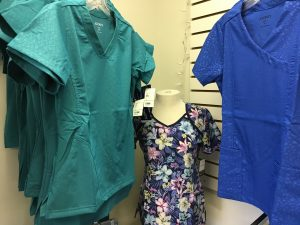 green and blue scrub tops hanging on racks